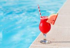 在游泳po附近的西瓜新鲜的汁圆滑的人饮料鸡尾酒 库存照片