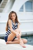在游艇俱乐部附近的美丽的女孩 库存图片