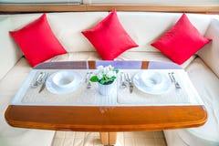 在游艇内部的豪华午餐桌设置 免版税库存图片