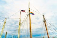 在游艇帆柱的两面旗子在Provincetown& x27;小游艇船坞,马萨诸塞 库存图片