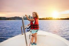 在游艇的孩子风帆在海 在小船的儿童航行 免版税库存图片