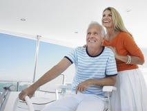 在游艇舵的微笑的夫妇  免版税库存照片