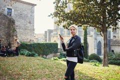 在游览之间的断裂期间年轻可爱的女性旅客使用手机 免版税库存图片