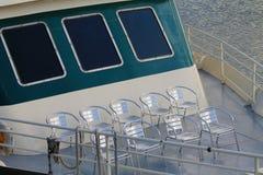 在游览小船前面甲板排队的轻便折叠躺椅 库存照片