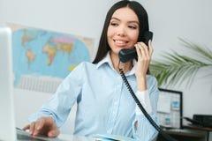 在游览机构答复电话浏览膝上型计算机的年轻女性旅行代理人顾问 图库摄影