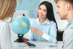 在游览机构通信的年轻夫妇与显示目的地的旅行代理人旅行的概念地球 库存图片