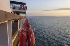 在游轮的甲板的橙色救护设备 免版税库存照片