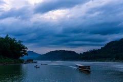 在湄公河的日落 与很多云彩的蓝色小时 有些小船在河 多云场面在琅勃拉邦,老挝 库存照片