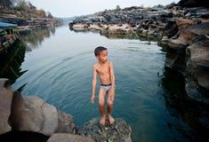 在湄公河的活动,游泳和演奏岩石的孩子钻孔石头 免版税库存图片