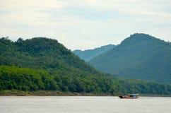 在湄公河,老挝的一条小船,变矮小由山 库存照片