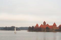 在湖乘快艇航行靠近特拉凯半岛在海岛上的城堡博物馆 Karaites,立陶宛,欧洲村庄  立陶宛landma 免版税库存图片