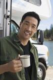在湖供以人员拿着咖啡杯在RV外面 图库摄影