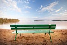 在湖前面的绿色长木凳 免版税库存照片