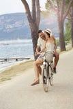 在湖区域供以人员运载他的一辆自行车的妇女 免版税图库摄影