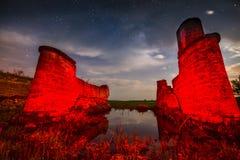 在湖反射的老夜城堡墙壁废墟与星天空a 免版税库存图片