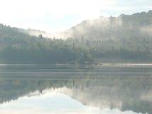 在湖反映的有薄雾的小山 库存照片