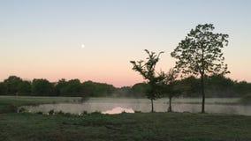 在湖反映的满月在与轻的雾的黎明 股票录像