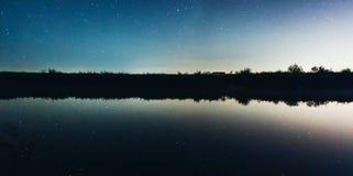 在湖反映的繁星之夜天空 免版税库存照片