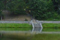 在湖台阶的一个石楼梯从一条路带领在下面湖 库存图片