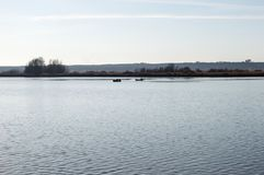 在湖和两条小船的秋天日落 库存图片