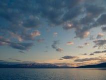 在湖和山后的金黄日落 免版税库存图片