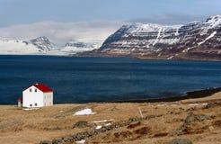 在湖和积雪覆盖的westfjords冰岛山附近的客舱 免版税库存照片