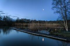 在湖和跳船的镇静平静的被月光照亮风景 图库摄影