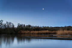 在湖和跳船的镇静平静的被月光照亮风景 免版税图库摄影