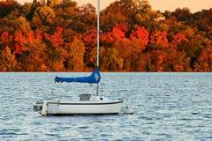 在湖哈丽的帆船反对五颜六色的秋天叶子 免版税图库摄影