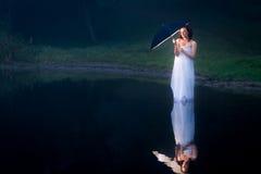 在湖妇女的反映有伞的 免版税库存图片