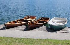 在湖岸停泊的三条划艇  图库摄影