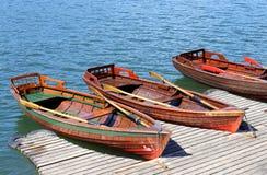在湖岸停泊的三条划艇  免版税库存图片