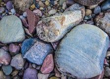 在湖岸找到的五颜六色的岩石 免版税库存照片