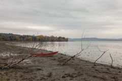 在湖岸的一条小的红色小船在一些骨骼树附近,在一喜怒无常的天 免版税图库摄影