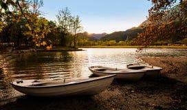 在湖岸的三条小船在日落 免版税库存照片