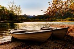 在湖岸的两条小船在日落 免版税图库摄影