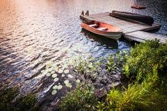 在湖岸的划艇在日出 免版税库存图片