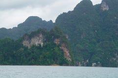 在湖岸的参天的石灰石山 免版税库存图片