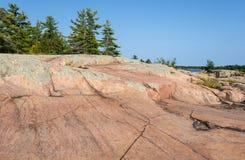 在湖岸的桃红色花岗岩岩石 免版税库存图片