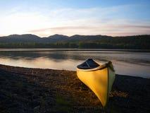 在湖岸的独木舟在黄昏。 免版税库存图片