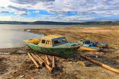 在湖岸的老小船 库存照片