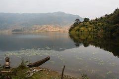 在湖岸的老木小船在尼泊尔 免版税库存照片