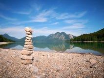 在湖岸的被堆积的小卵石 平衡栈石头 图库摄影