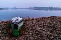 在湖岸的被翻转的小船 免版税库存图片