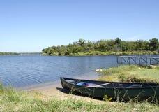 在湖岸的绿色独木舟 免版税库存照片