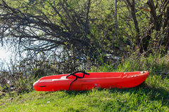 在湖岸边缘拔的一艘小儿童皮船 库存图片