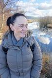 在湖旁边的愉快,微笑的妇女 免版税库存图片