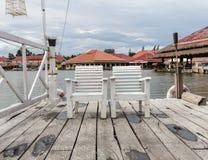 在湖旁边的空白木椅子。 库存图片