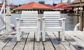 在湖旁边的空白木椅子。 免版税库存照片