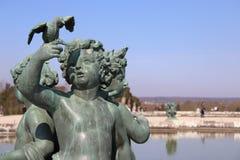 在湖旁边的雕象Versailles'城堡的 免版税库存图片